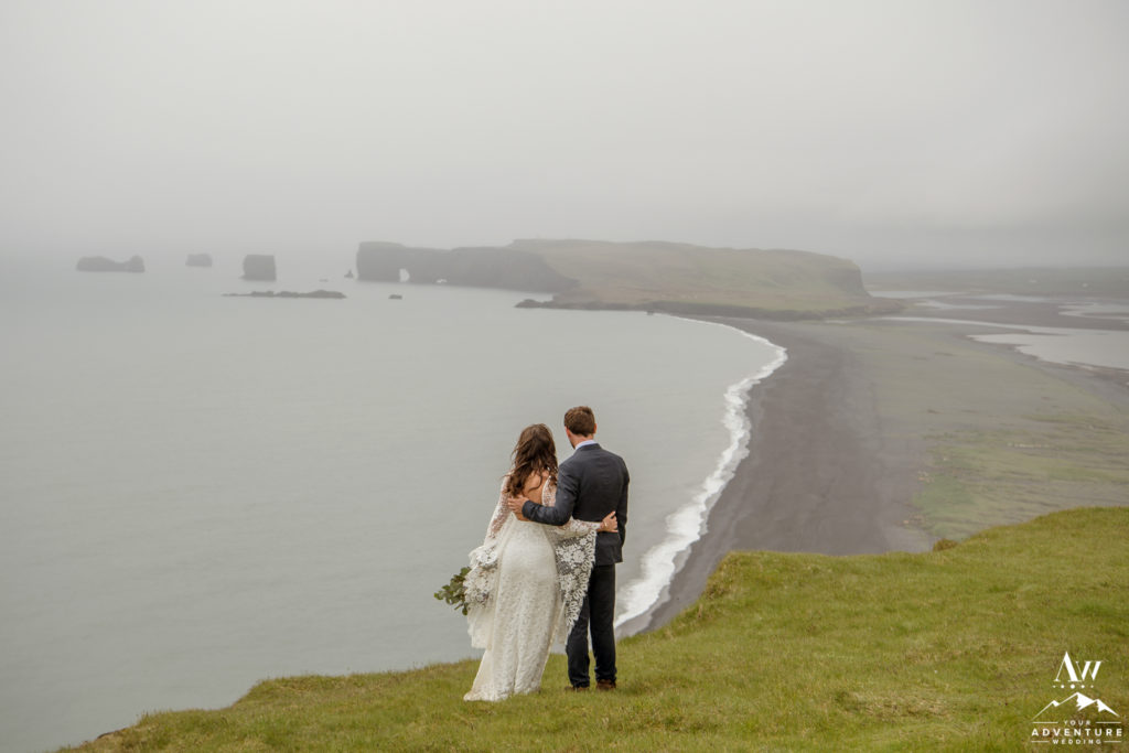 Iceland wedding couple looking out from reynisfjall mountain