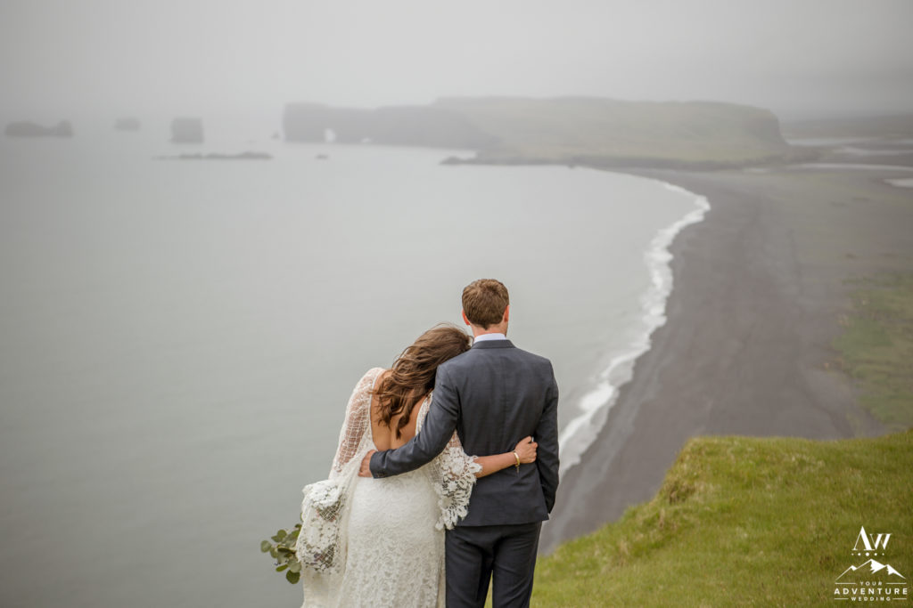 Bride and Groom in Iceland looking at towards Dyrholaey