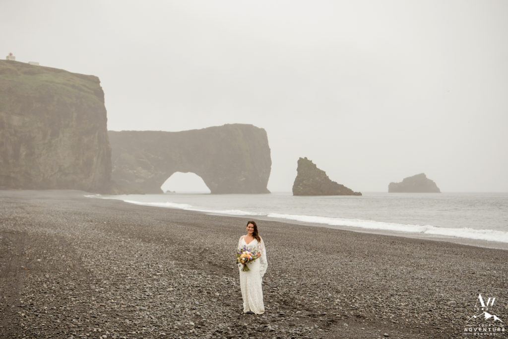 Iceland Elopement Bride standing in front of Dyrholaey Sea Arch