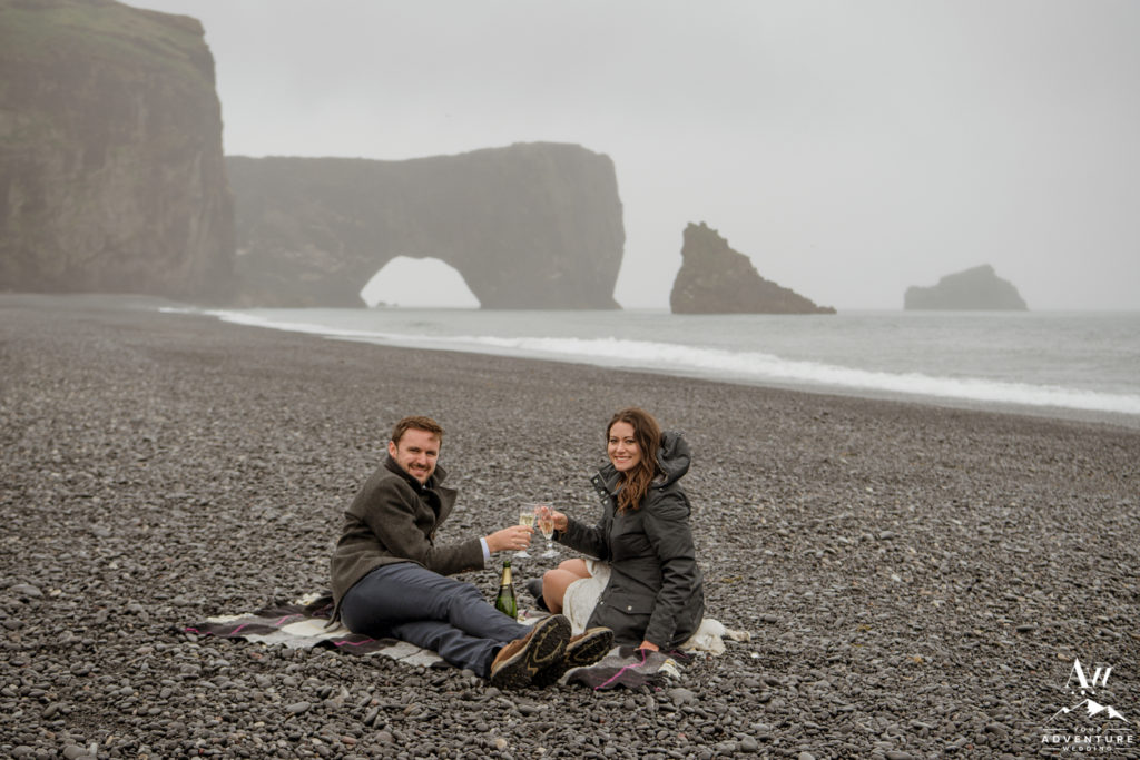 Iceland Wedding couple at Dyrholaey Sea Arch for champagne picnic