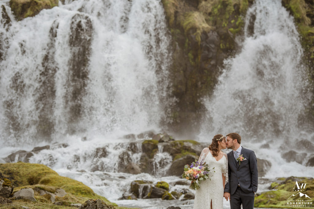 Iceland Elopement Couple kissing in front of a waterfall