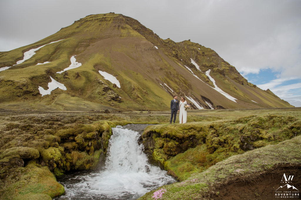 Iceland Wedding Couple standing on a waterfall