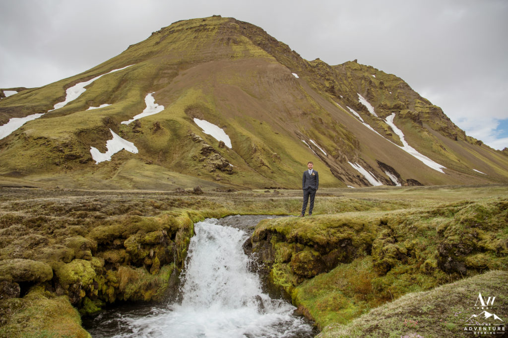 Groom standing on top of a Iceland Waterfall