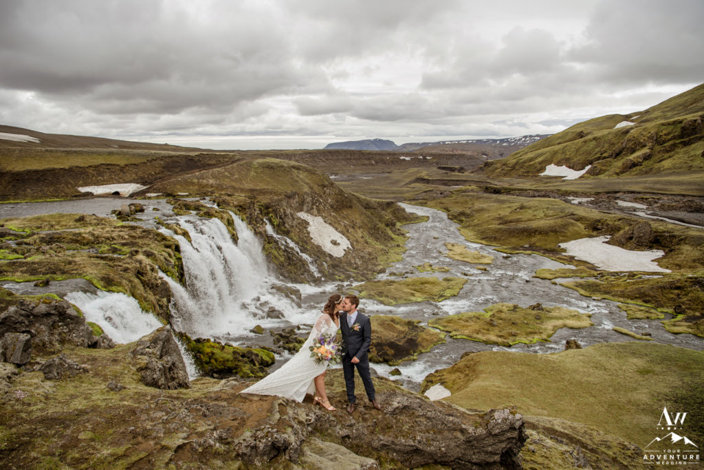 Adventurous Iceland Elopement couple kissing in front of a waterfall