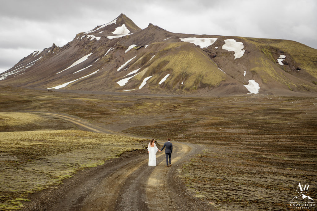 June Elopement in Iceland couple walking on a highland road