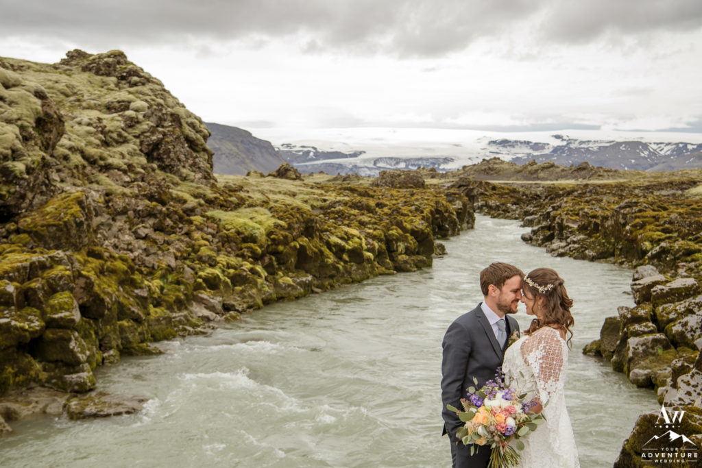 Adventurous Wedding Couple in front of a glacier river
