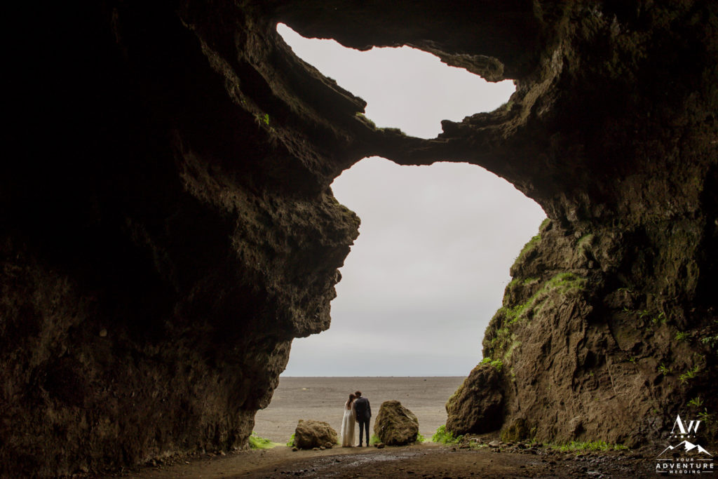 Couple kissing inside of hjorleifshofdi cave in Southern Iceland