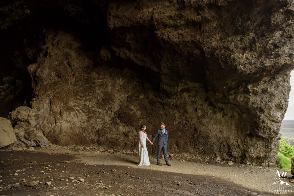 Iceland Elopement Couple walking inside of hjorleifshofdi cave