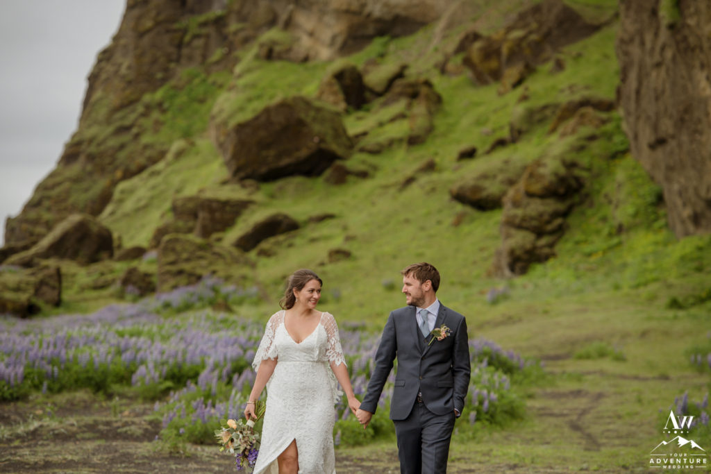 Iceland Wedding Couple walking in field of lupines