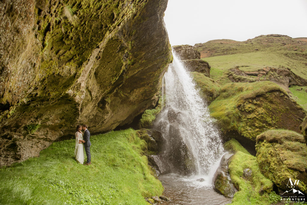 Adventurous Elopement Couple standing behind a waterfall