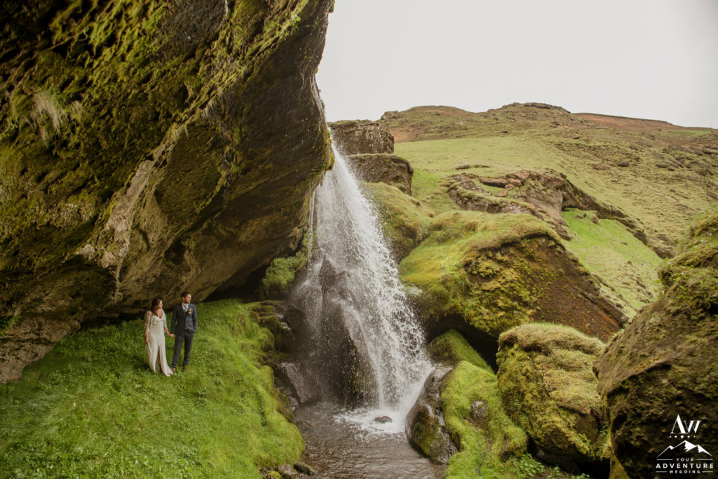 Adventurous Iceland Wedding Couple standing behind a waterfall