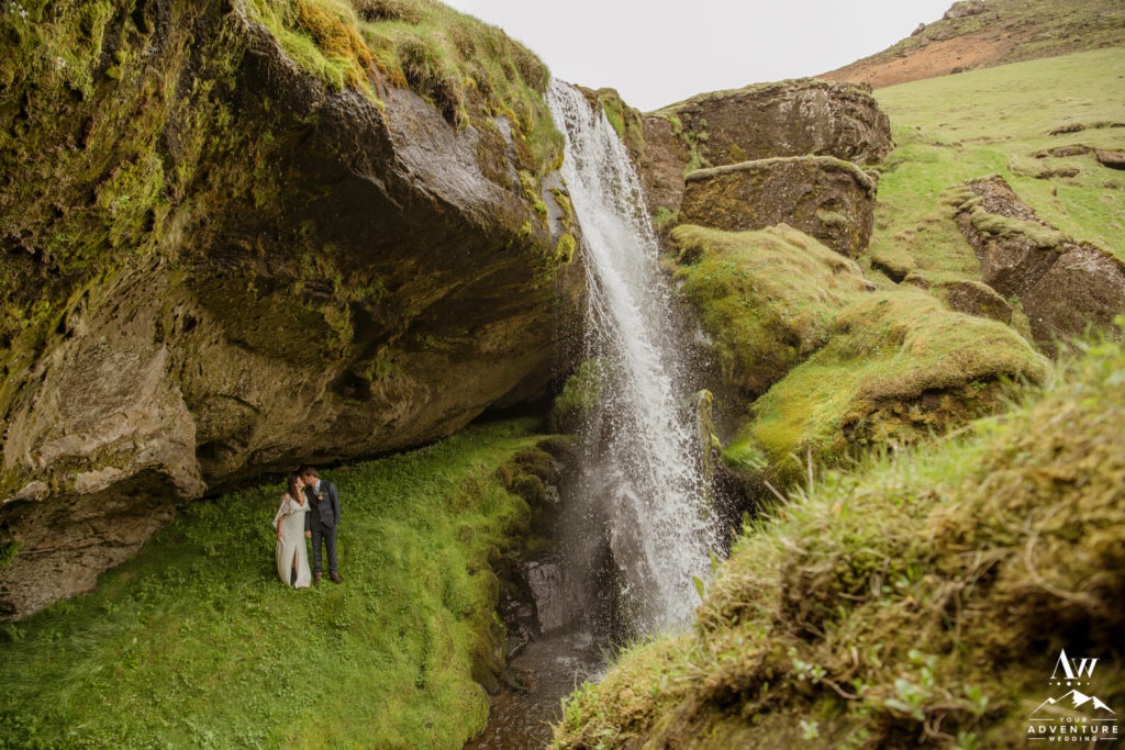 Couple standing behind a waterfall on Iceland Wedding day