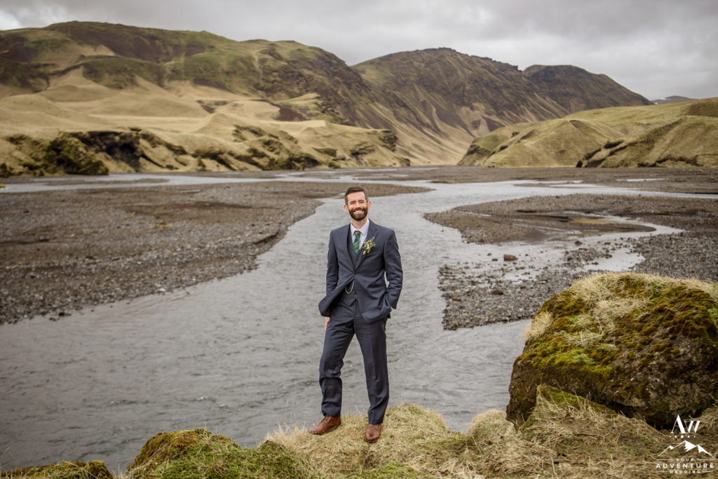 Groom standing in front of a private canyon in Iceland