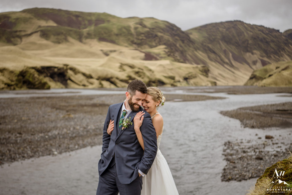 Bride hugging her groom from behind on adventure wedding day