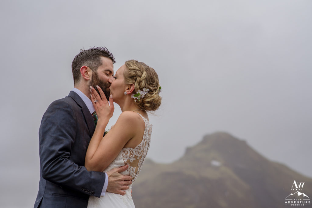 Adventurous couple kissing in the rain at a glacier