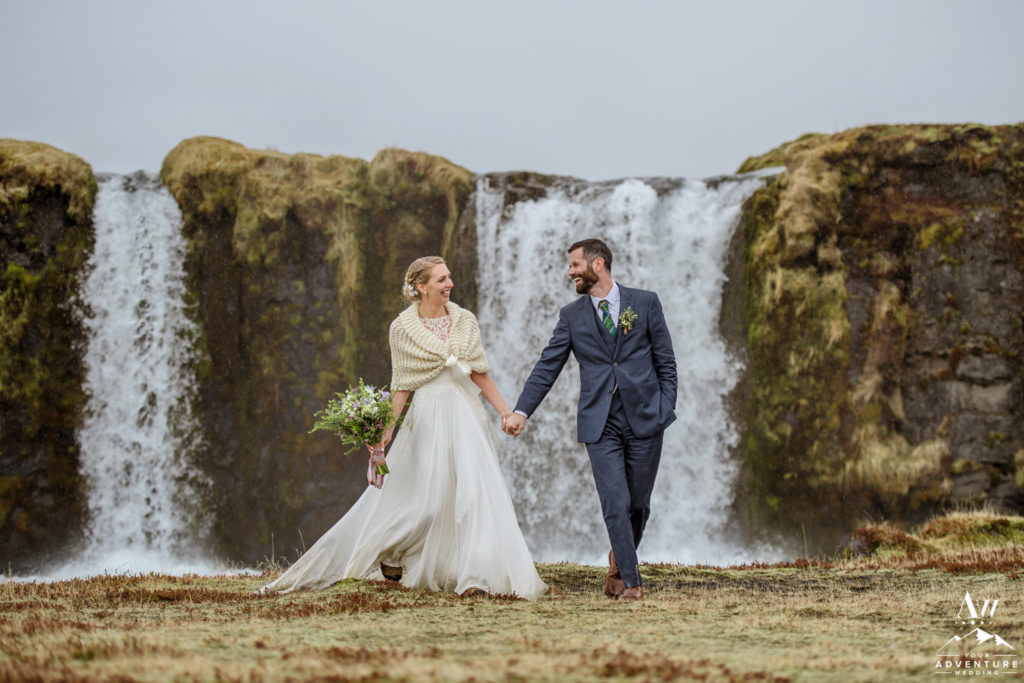 Couple walking in front of a private waterfall on wedding day