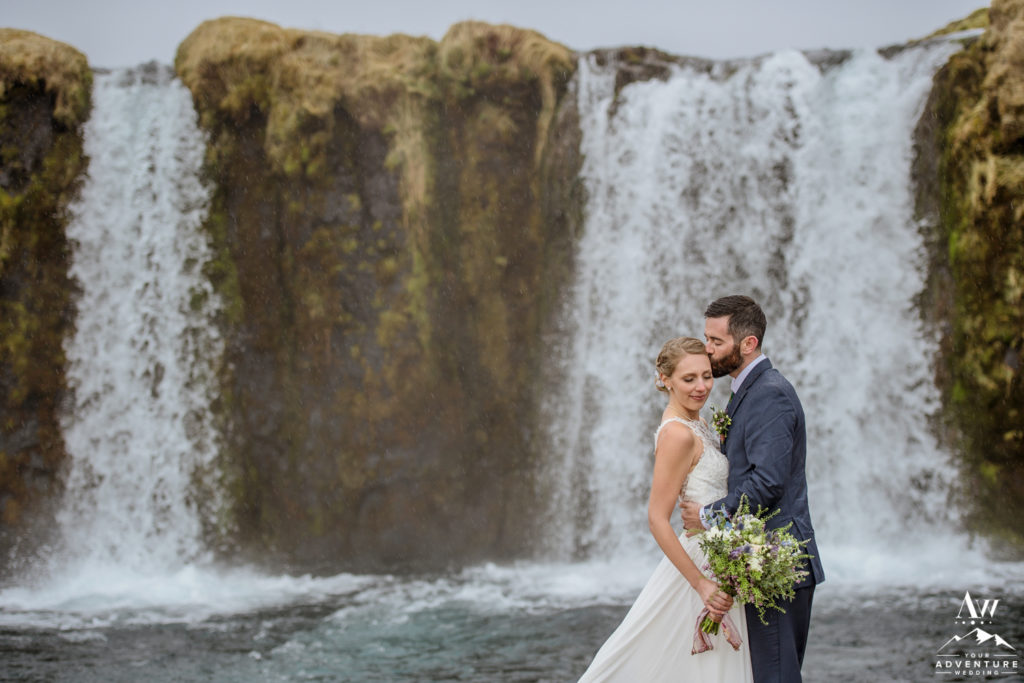 Groom kissing the bride on the forehead at a private waterfall