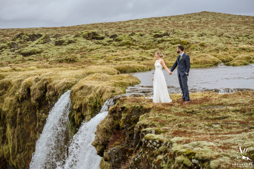 Couple standing on top of a private waterfall