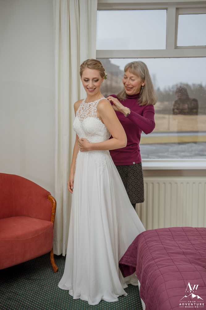 Mother helping daughter get into her Iceland Wedding Dress
