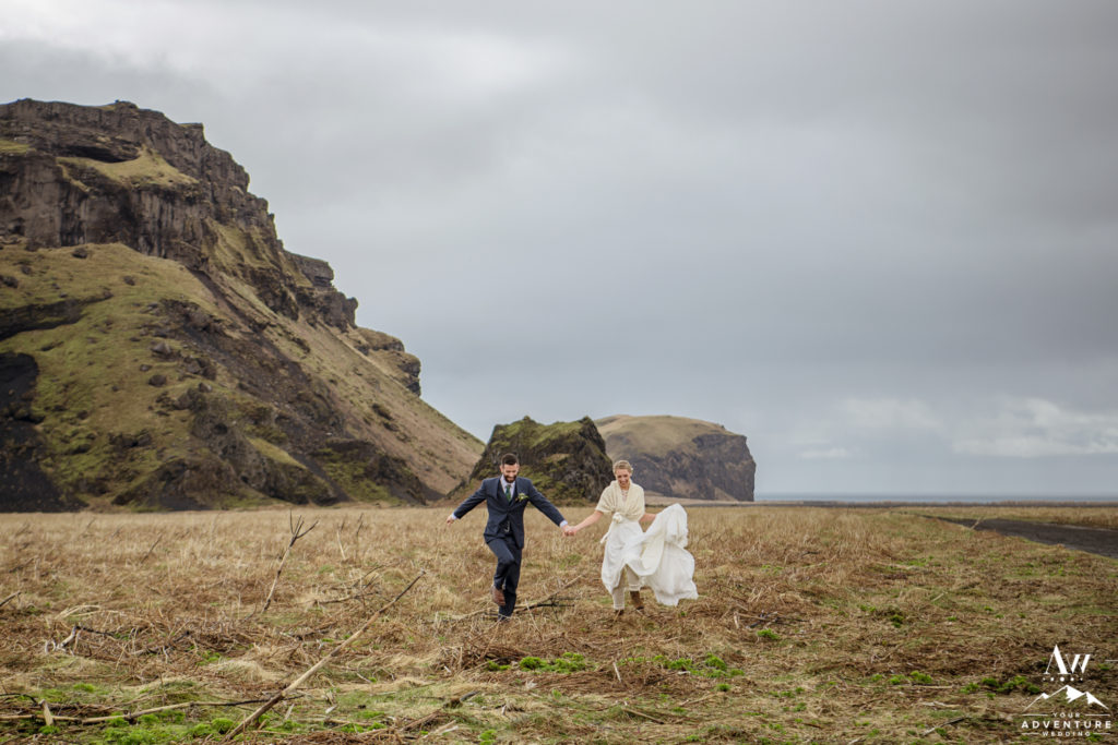 Iceland Wedding Couple running outside of hjorleifshofdi cave