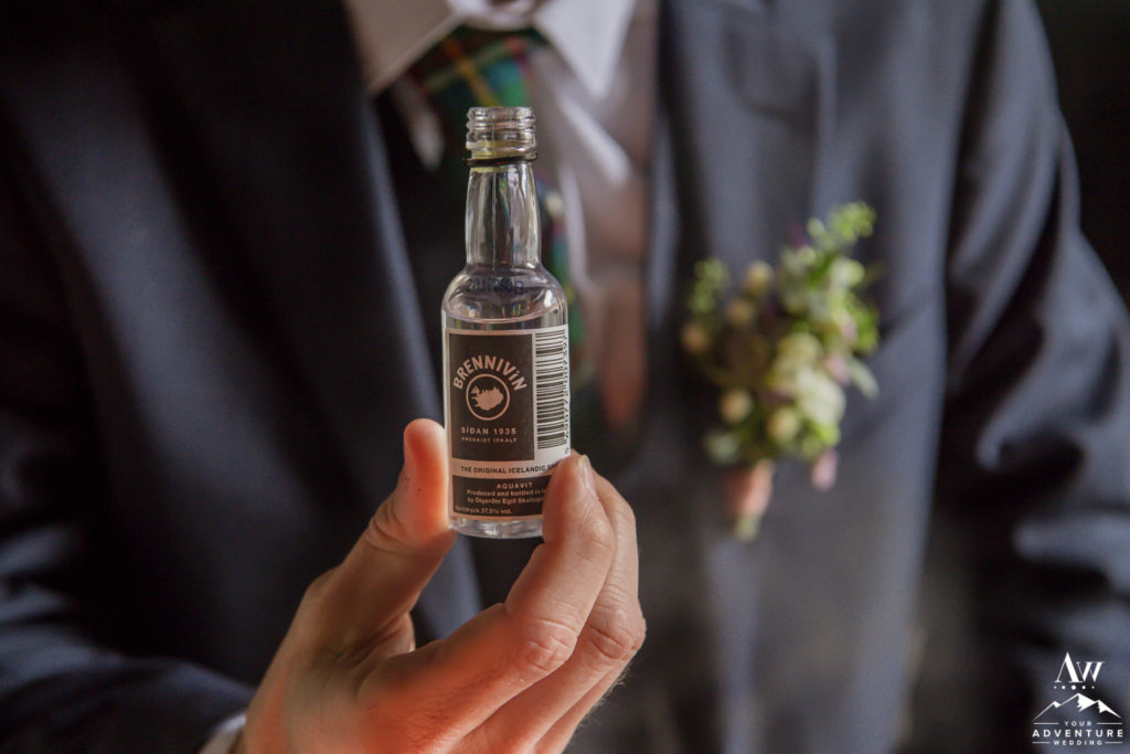 Iceland Wedding Groom holding a shot of Brennivin