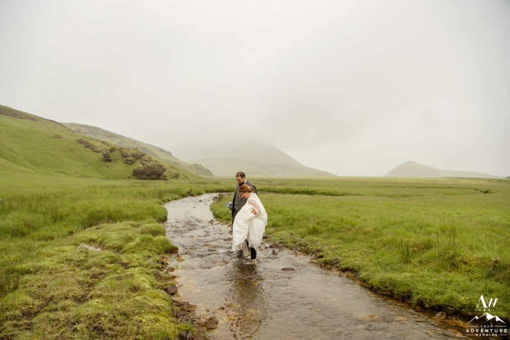 Adventure wedding couple hiking through a river