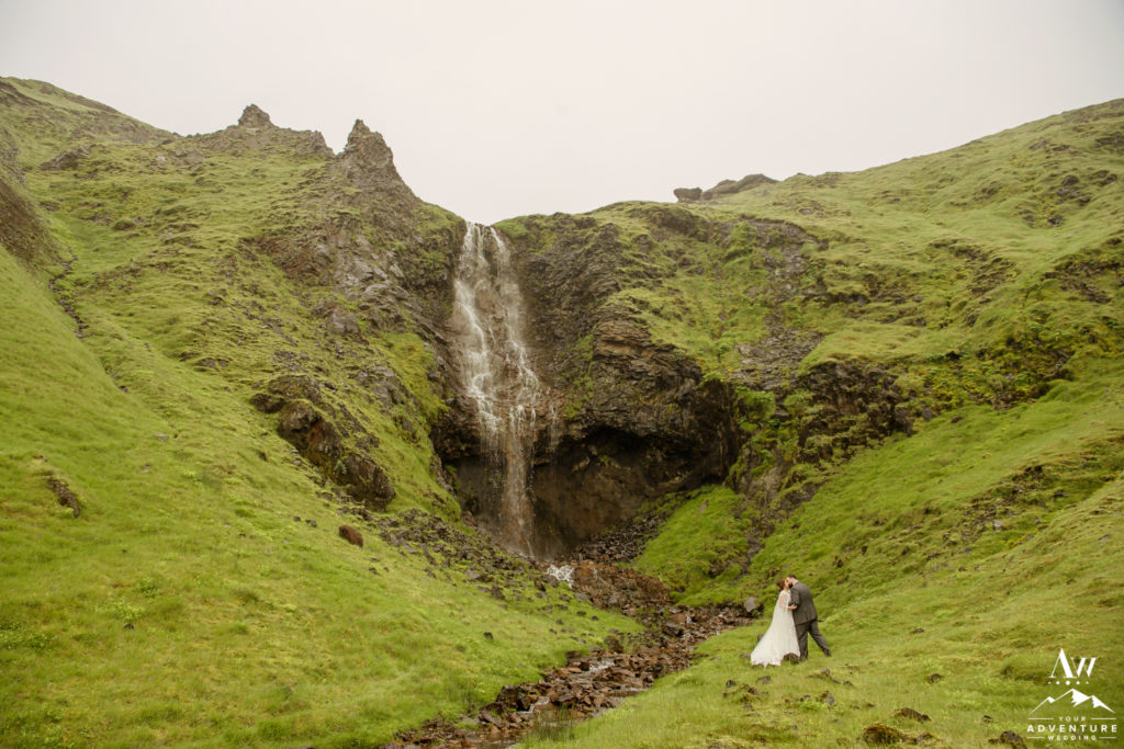 Adventurous couple in Iceland in front of a offbeat waterfall