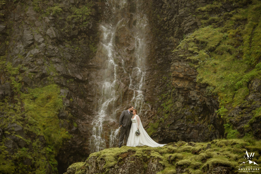 Couple kissing in front of offbeat waterfall