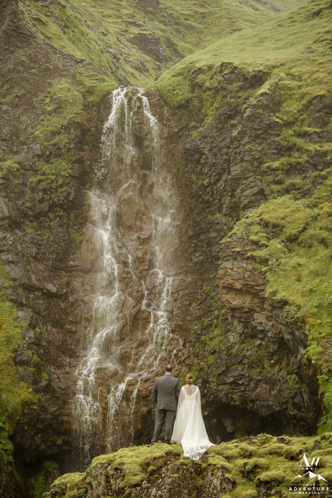 Iceland adventure wedding couple looking at private waterfall