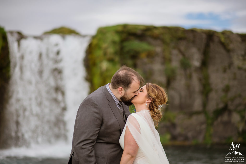 Iceland Wedding couple kiss in front of a waterfall