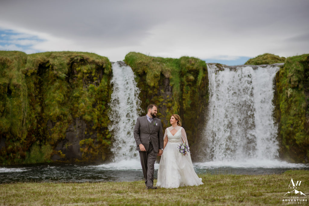 Iceland Wedding Couple walking in front of a private waterfall