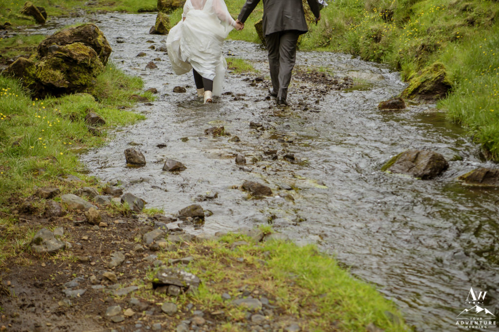 Iceland elopement couple hiking through a river