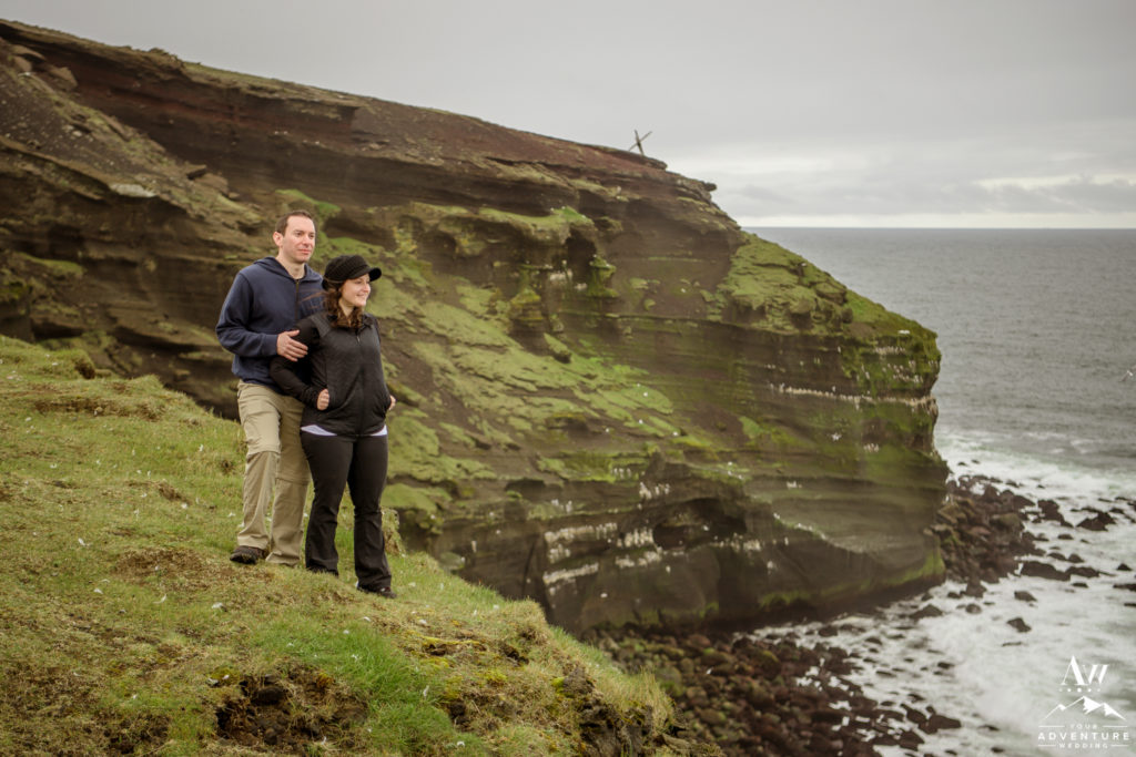 Engaged Photo couple looking out from a cliff