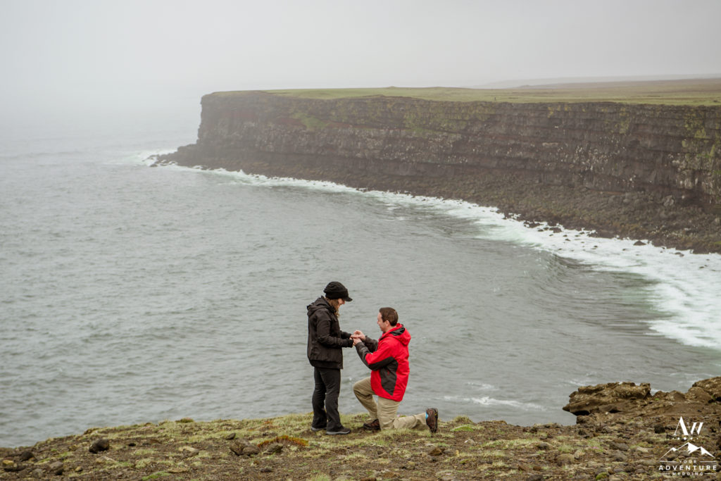 Man proposing on a cliff in Iceland
