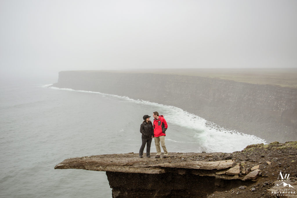 Couple standing on cliff with golden cliffs behind