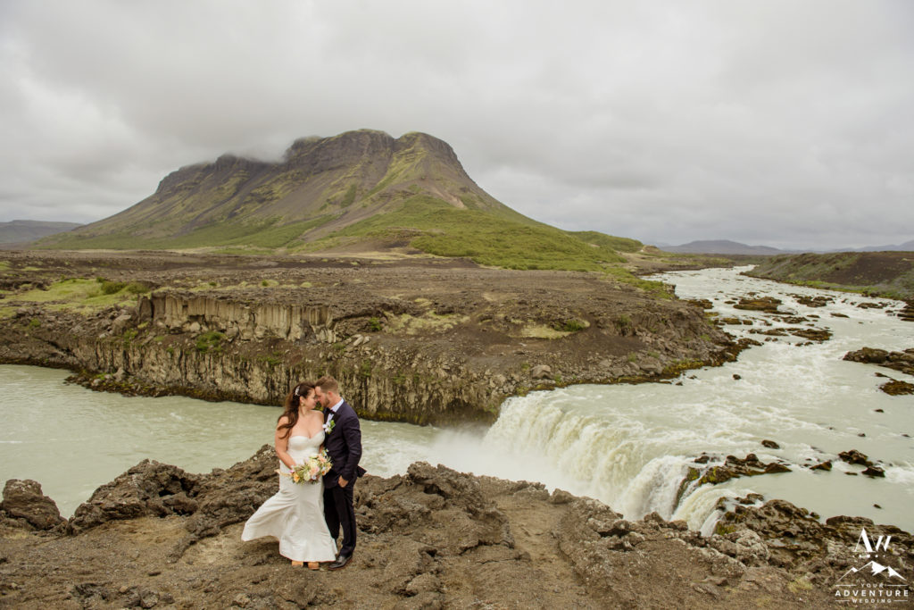 Iceland Wedding Couple in front of a dramatic mountain and waterfall