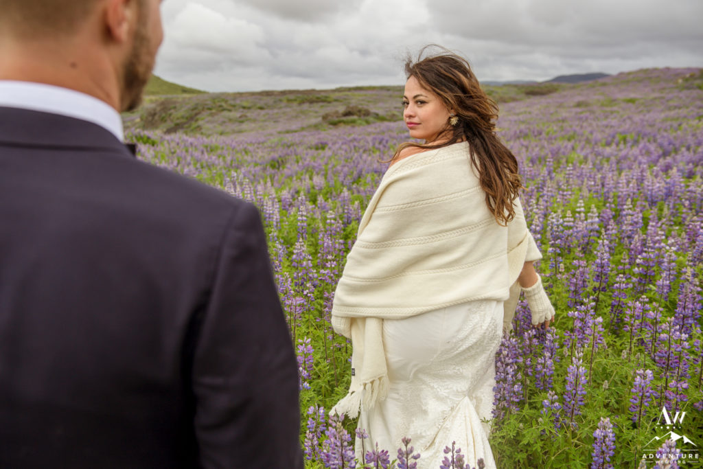 Iceland Wedding Bride looking back at her groom in lupine