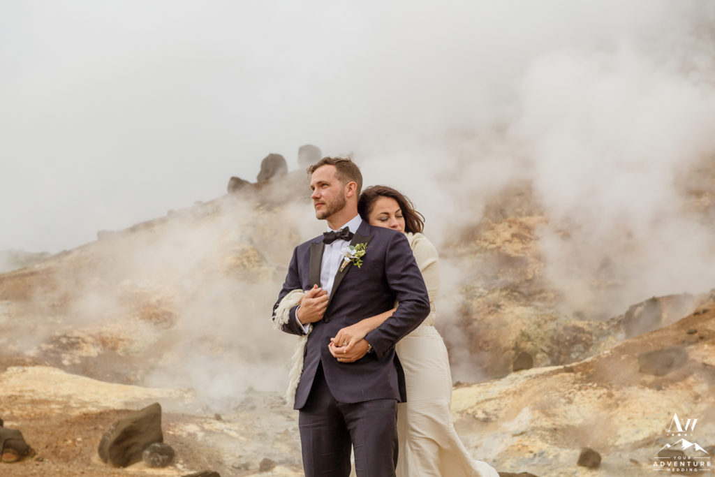 Bride hugging her groom at geothermal area in Iceland
