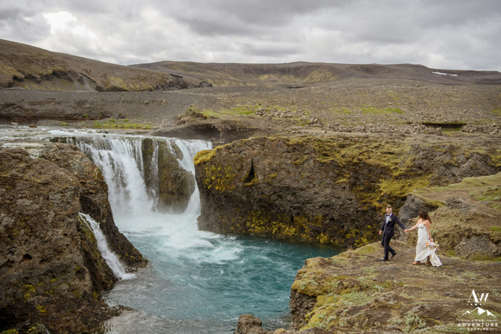 Bride and Groom Exploring a hidden waterfall in Iceland