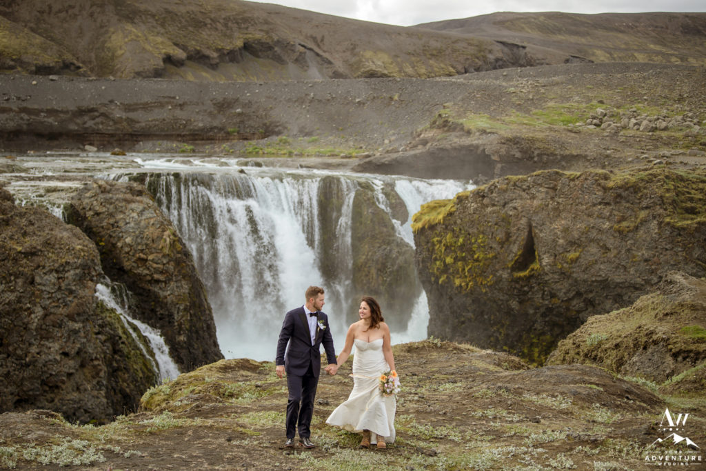 Couple walking in front of hidden waterfall in Iceland
