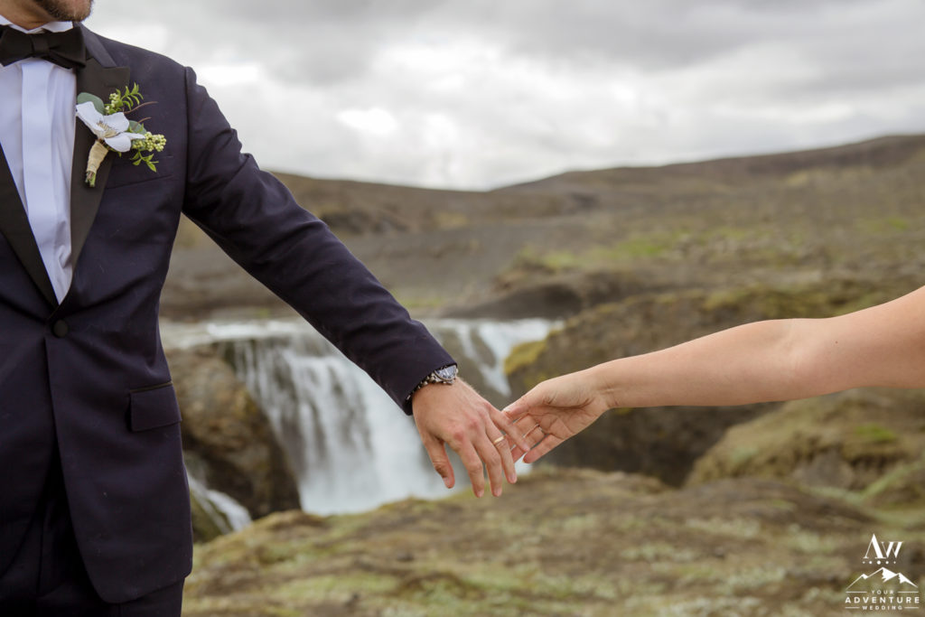 Iceland Wedding Couple holding hands in front of a waterfall