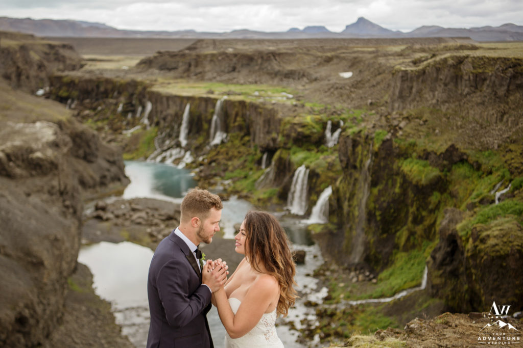 Couple cuddling at Iceland Waterfall that looks like Jurassic Park
