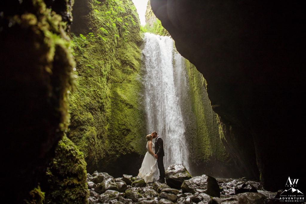 Wedding couple exploring a secret waterfall