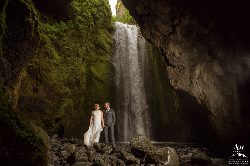 Iceland wedding couple adventuring in a waterfall