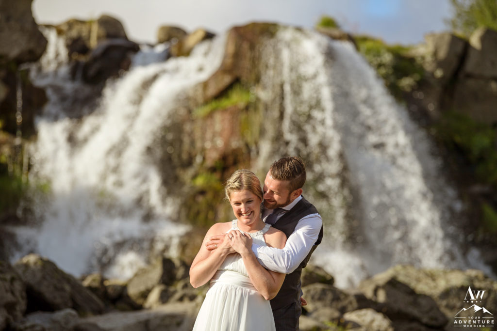 Couple cuddling in front of a waterfall