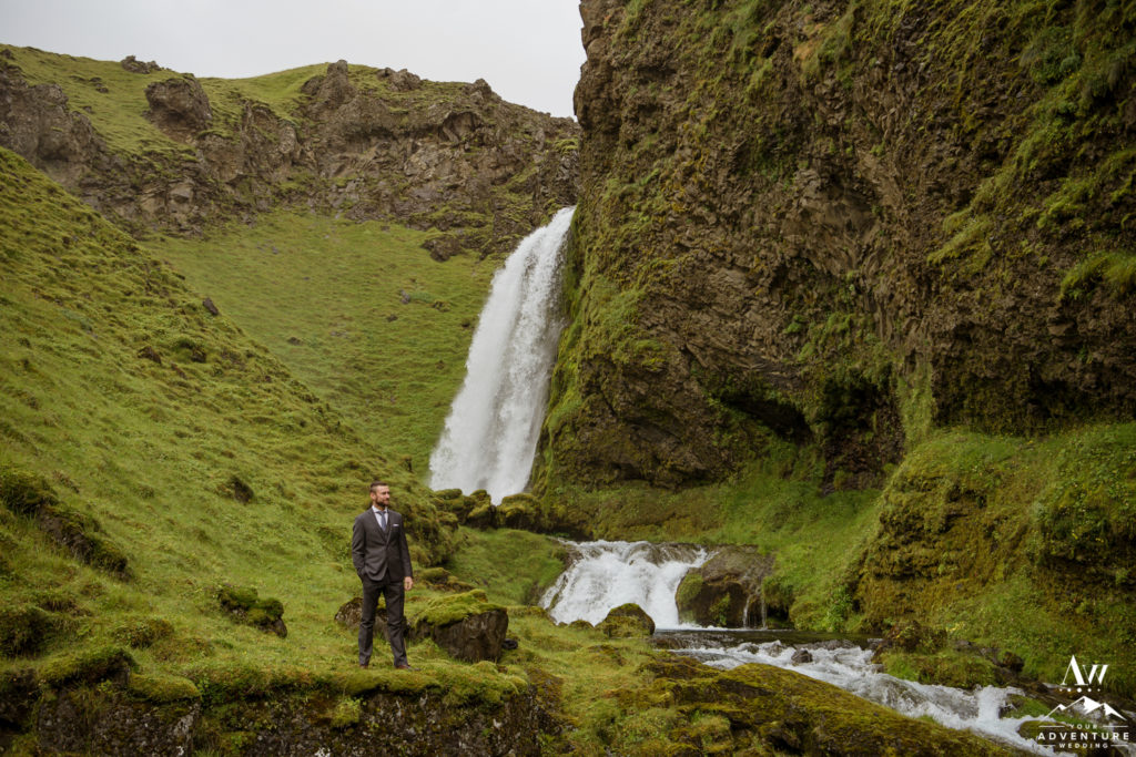 Iceland Groom standing in front of a waterfall