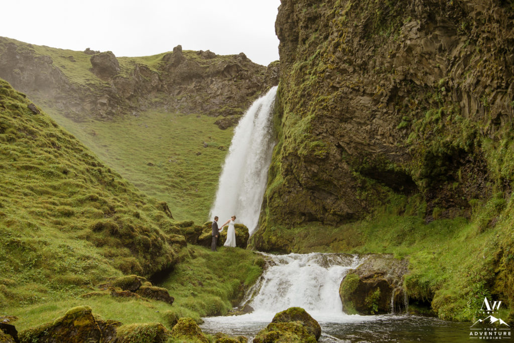 Couple exploring Iceland private waterfall