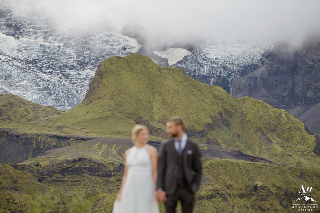 Couple looking at each other in front of a glacier outlet