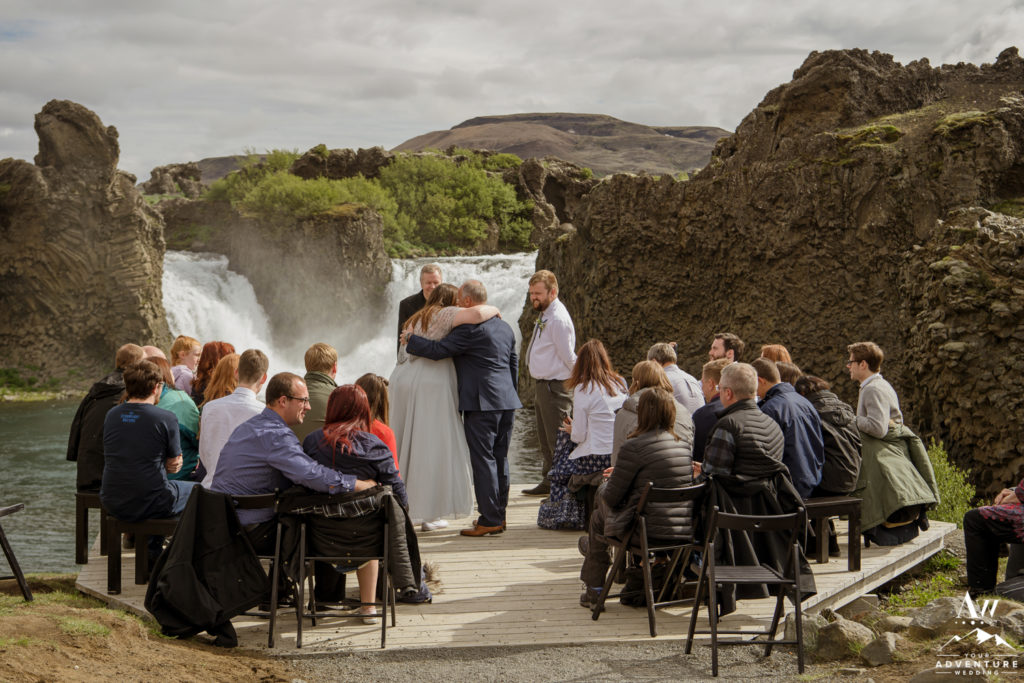 Father of the bride giving away his daughter at Hjalparfoss Waterfall