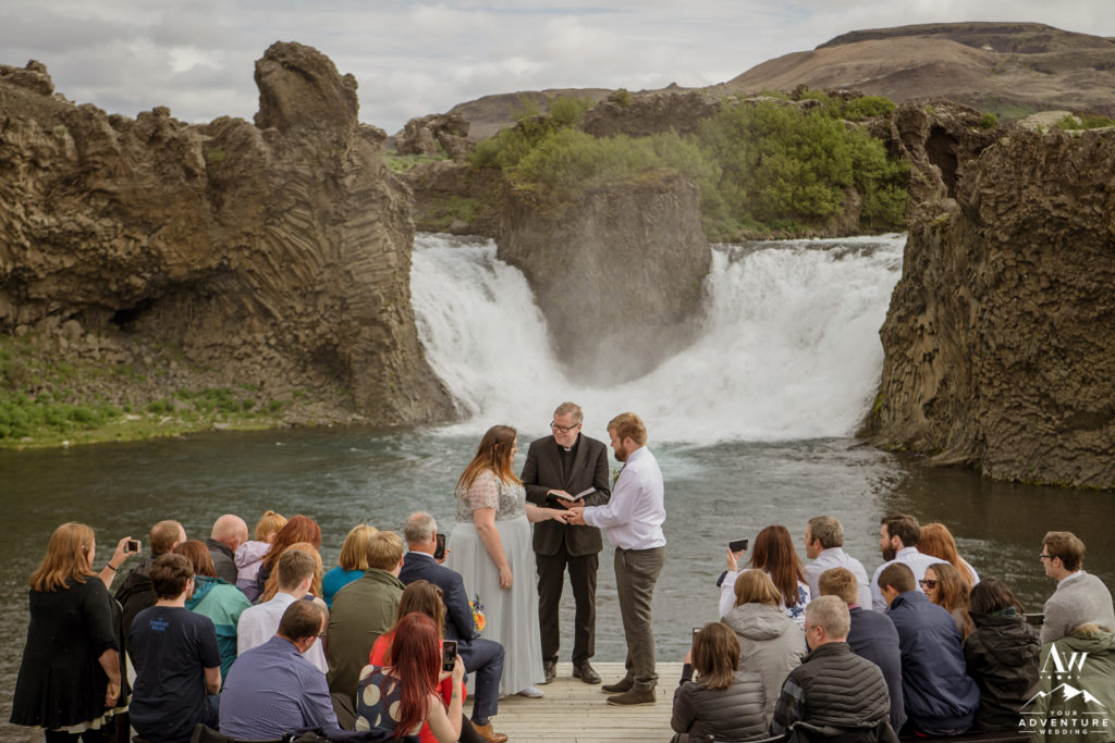 Iceland Wedding Ceremony Couple Exchanging Rings at Hjalparfoss Waterfall